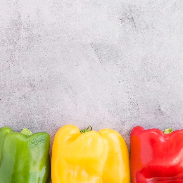 Green; yellow and red bell pepper on grey concrete backdrop Free Photo