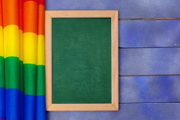 木製の背景と空白greenboardに明るい虹ゲイフラグ Premium写真