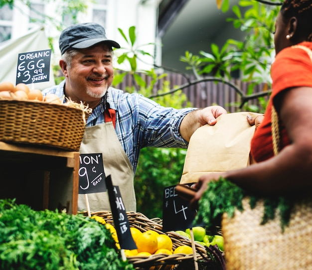 Greengrocer selling organic fresh agricultural product at farmer market Premium Photo