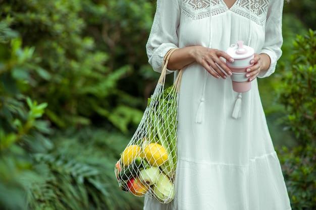 温室。野菜の袋と手のこぼれ防止カップの白いドレスを着た女性 Premium写真