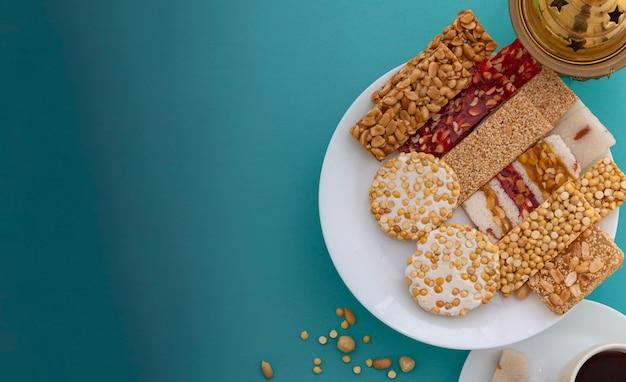 Greeting card of traditional mawlid dessert on blue Premium Photo