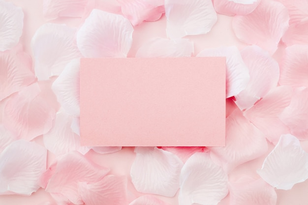 Greeting card on white and pink rose petals Free Photo
