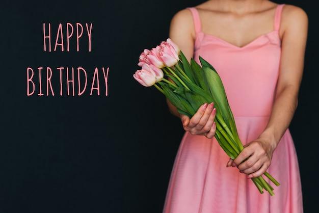 碑文お誕生日おめでとうグリーティングカード。手にピンクのチューリップの花束 Premium写真