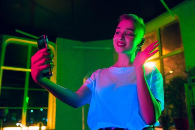 Saluto. ritratto cinematografico di donna alla moda in interni illuminati al neon. tonica come effetti cinematografici, colori luminosi al neon. modello caucasico utilizza lo smartphone in luci colorate al chiuso. cultura giovanile. Foto Gratuite