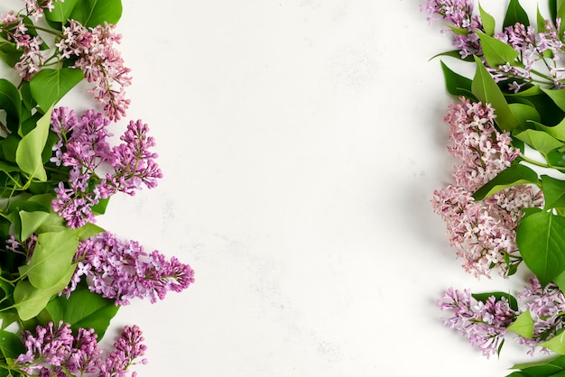 Greeting frame from fresh lilac flowers with green leaves on a light grey marble background. top vie