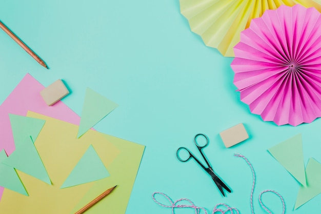 Greeting paper; pencil; scissor; eraser and circular flower paper on teal backdrop Free Photo