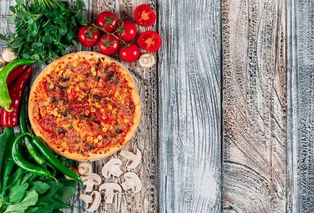 Пицца взгляд сверху с перцами, грибами, томатами и grenery на светлой предпосылке штукатурки. вертикальный Бесплатные Фотографии