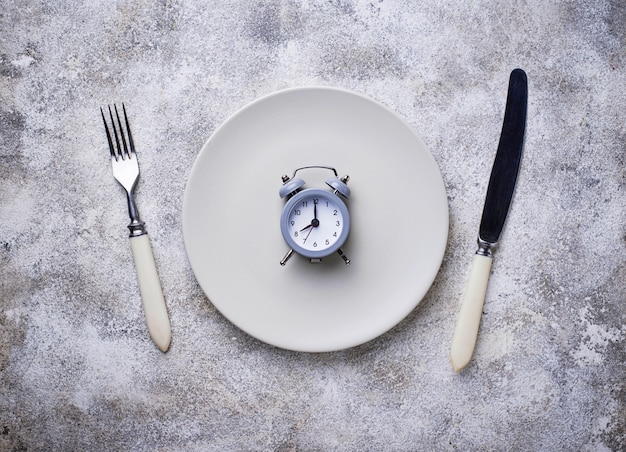 Grey alarm clock in empty plate. Premium Photo