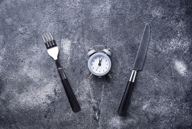 Grey alarm clock with knife and fork Premium Photo