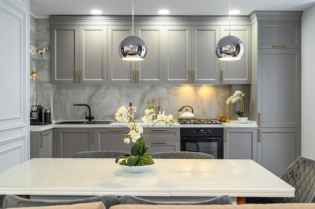 Серо-белый современный классический интерьер кухни с обеденным столом в современном стиле, вид спереди Premium Фотографии
