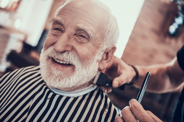 Grey haired adult smiles during nape haircutting. Premium Photo