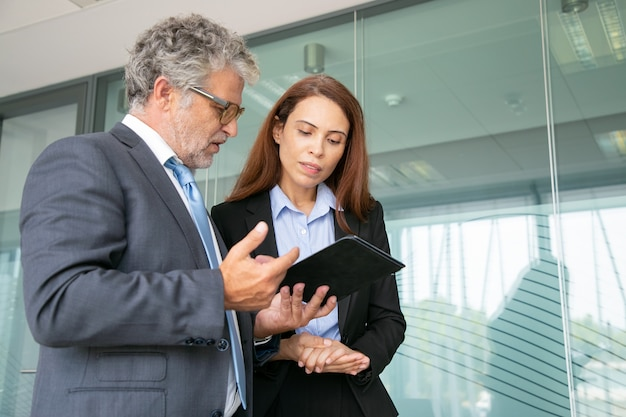Grey-haired boss discussing with assistant, holding tablet and standing in conference room Free Photo