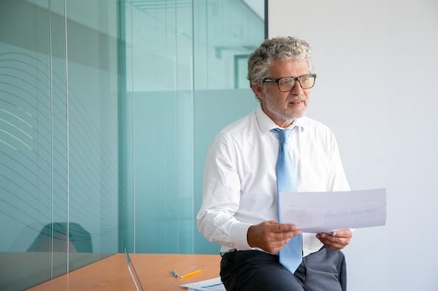 テーブルの上に座って紙を保持している白髪の白人実業家 無料写真