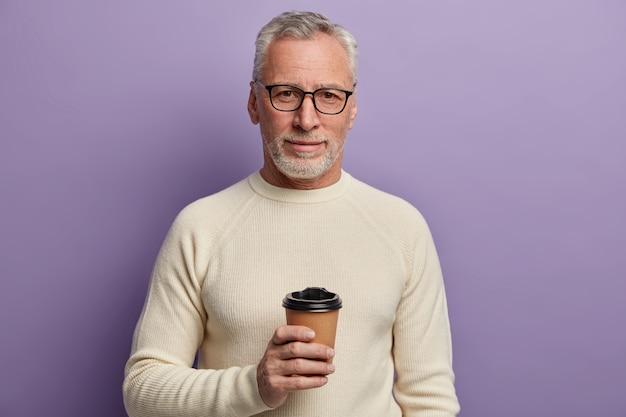 L'uomo anziano dai capelli grigi indossa occhiali trasparenti e maglione bianco, si alza e raffredda la bevanda calda, gode di una piacevole conversazione, pone su sfondo viola. Foto Gratuite