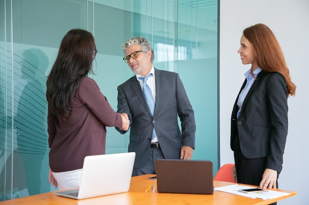 Grey-haired senior manager handshaking and greeting businesswoman Free Photo
