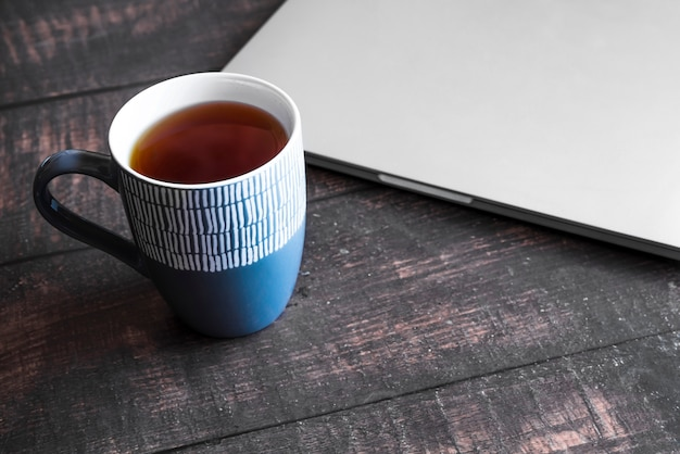 Grey laptop with coffee on wooden table Free Photo
