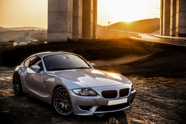Automobile sportiva grigia grigia di colore nel tramonto. Foto Gratuite