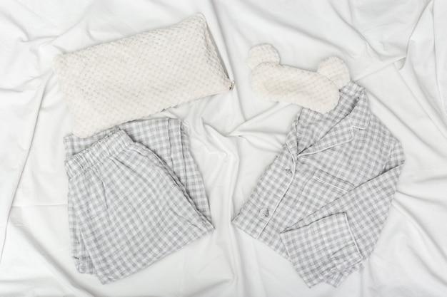 회색 잠옷, 수면 마스크, 흰색 구겨진 시트에 부드러운 푹신한 쿠션. 프리미엄 사진