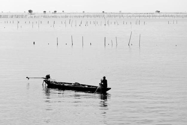 Ripresa in scala di grigi di una persona su un motoscafo in mezzo al mare calmo Foto Gratuite