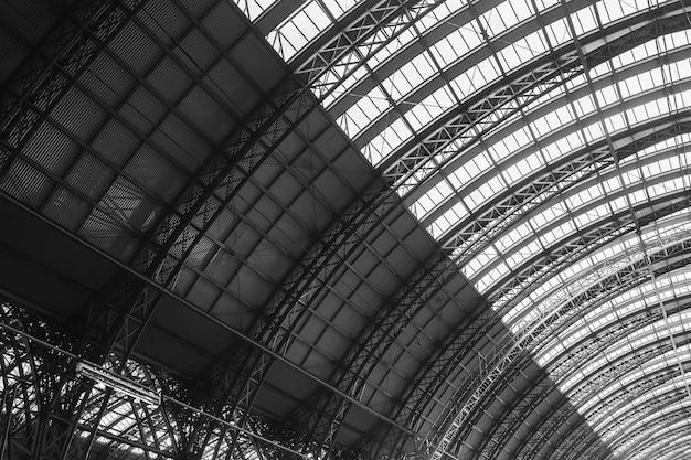 Scala di grigi della stazione ferroviaria centrale sotto la luce del sole a francoforte in germania Foto Gratuite