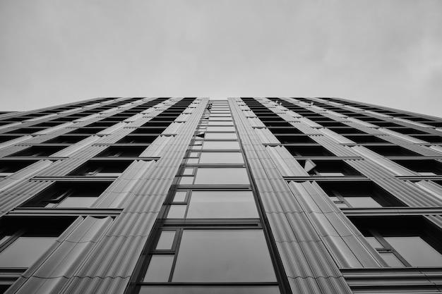 Scala di grigi di un moderno grattacielo sotto il cielo nuvoloso Foto Gratuite
