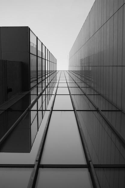 햇빛 아래 유리창이있는 현대적인 건물의 지붕의 회색조 무료 사진