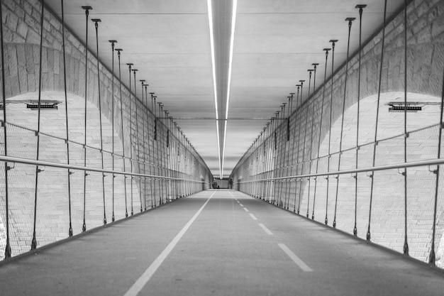 Оттенки серого на туннеле, окруженном огнями в дневное время Бесплатные Фотографии