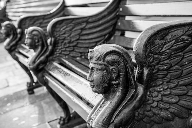 Scatto in scala di grigi delle panchine in pietra splendidamente decorate catturato a londra, inghilterra Foto Gratuite