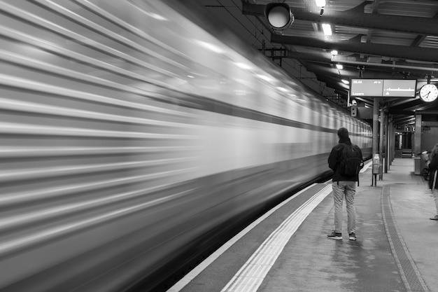Scatto in scala di grigi di un uomo in attesa di un treno nella stazione e un treno sfocato in movimento Foto Gratuite