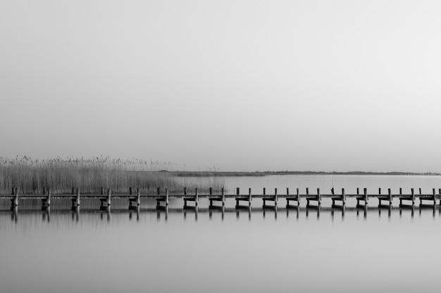 Серый снимок деревянного пирса у моря в дневное время Бесплатные Фотографии