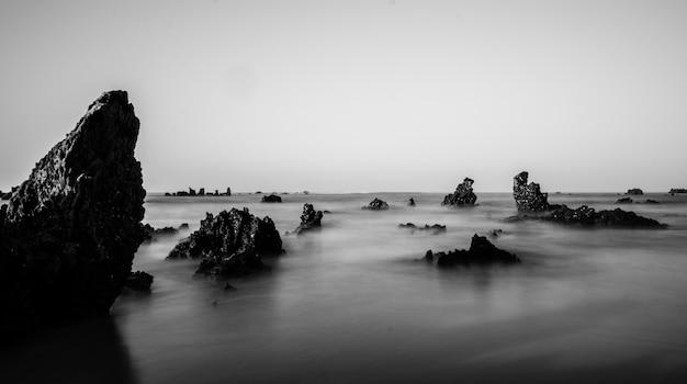 海の岩層のグレースケールショット 無料写真