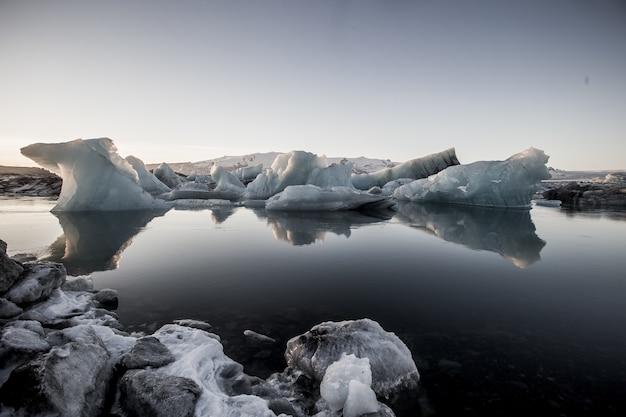 アイスランド、雪に覆われたヨークルスアゥルロゥンの凍った水の近くの氷山のグレースケールショット 無料写真