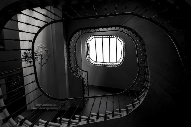 건물의 나선형 계단의 회색조 샷 무료 사진