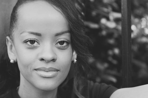 Scatto in scala di grigi di una donna afroamericana sorridente Foto Gratuite