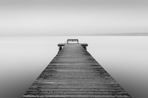 Colpo in scala di grigi di un cane di legno vicino al mare con uno sfondo nebbioso Foto Gratuite