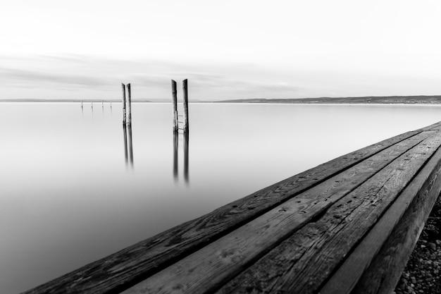 Colpo in scala di grigi di un molo in legno vicino al mare sotto il bel cielo nuvoloso Foto Gratuite