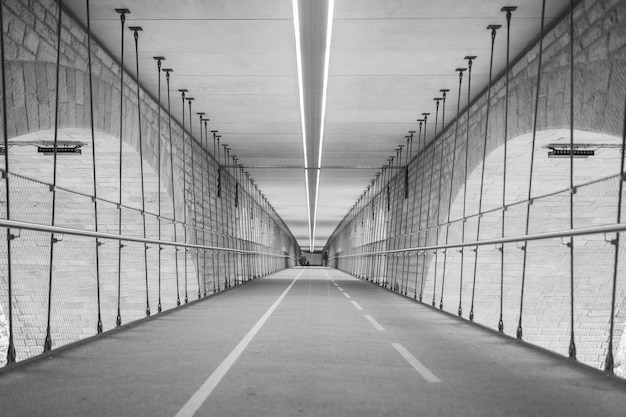 Greyscale of a tunnel surrounded by the lights during daytime Free Photo