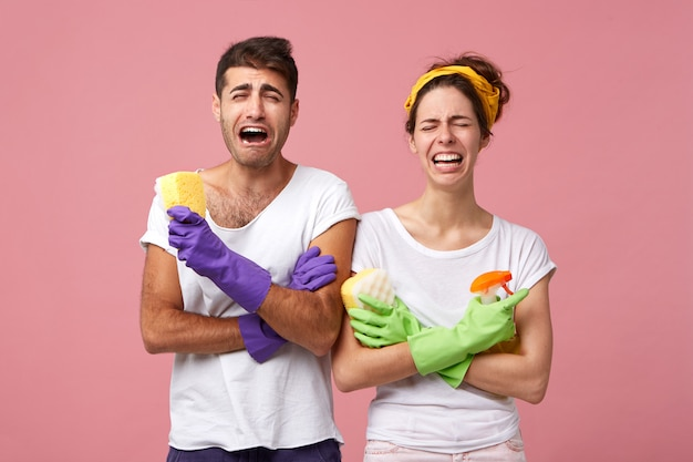 Скорбящая пара в белых футболках и перчатках с губками и спреем для стирки расстроена тем, что не хочет заниматься уборкой по выходным. мужчина и женщина с расстроенным выражением лица собираются убираться в доме Бесплатные Фотографии