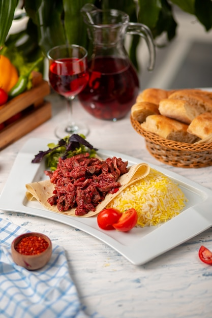 Grilled bbq beef meat slices, doner in lavash with green salad, tomatoes and rice garnish Free Photo