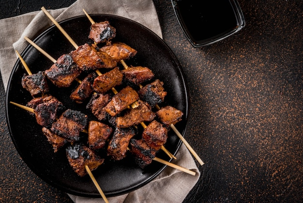Grilled beef liver on skewers, with teriyaki or soy sauce, yakitori, dark rusty  table  top view Premium Photo