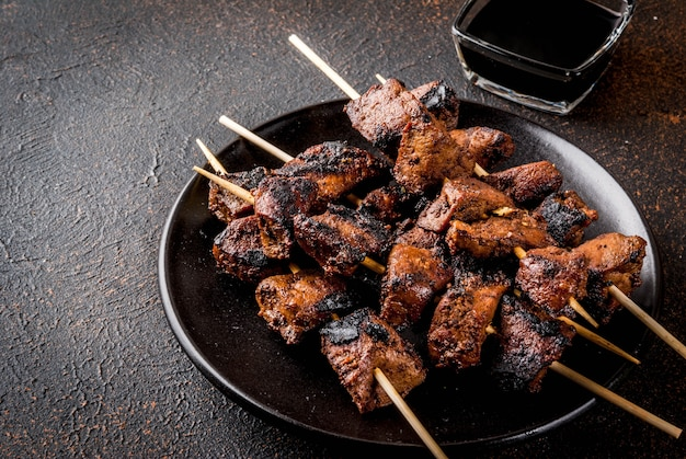 Grilled beef liver on skewers, with teriyaki or soy sauce, yakitori Premium Photo