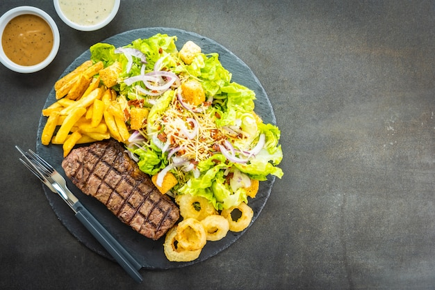 Grilled beef meat steak with french fries onion ring Free Photo