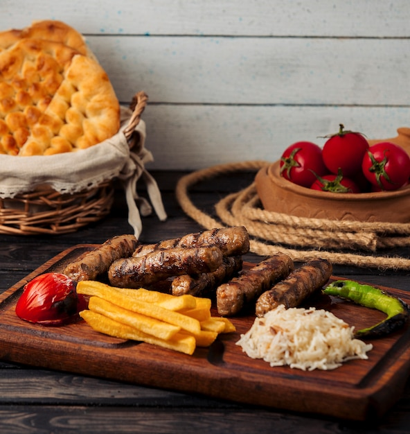 Grilled beef sausages with rice, french fries, pepper and tomato Free Photo