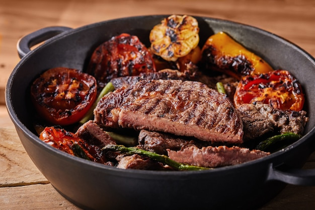 Grilled beef steak in a black pan with baked vegetables - tomatoes, asparagus, garlic and peppers Premium Photo