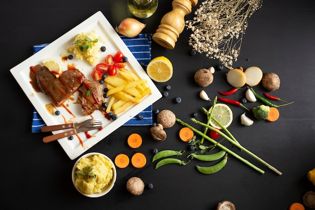 Grilled beef steak and potato vegetables on dark wooden table background, top view. juicy meat dish with sauce, potato ,peppers and cutlery in disk. restaurant food Premium Photo