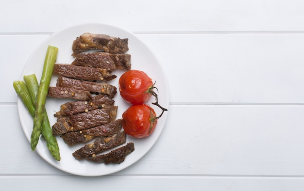 Grilled beef steak on a white plate and white background, flat lay and copy space Premium Photo