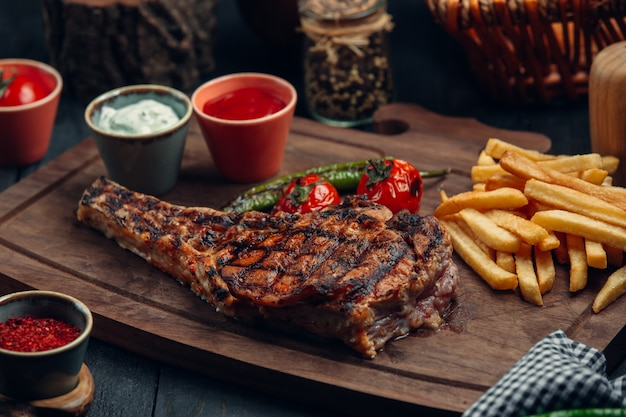 Grilled beef steak with fries, grilled tomato, pepper and sauces Free Photo