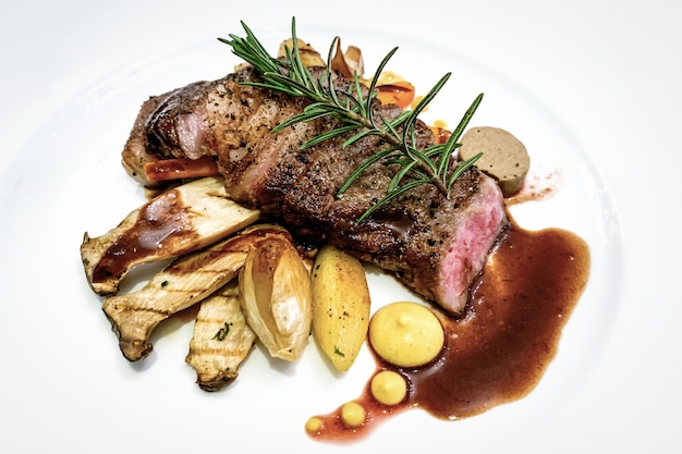 Grilled beef  steak with herbs on white plate Premium Photo