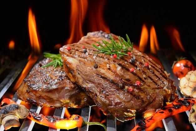 Grilled beef steak with vegetable on the flaming grill Premium Photo
