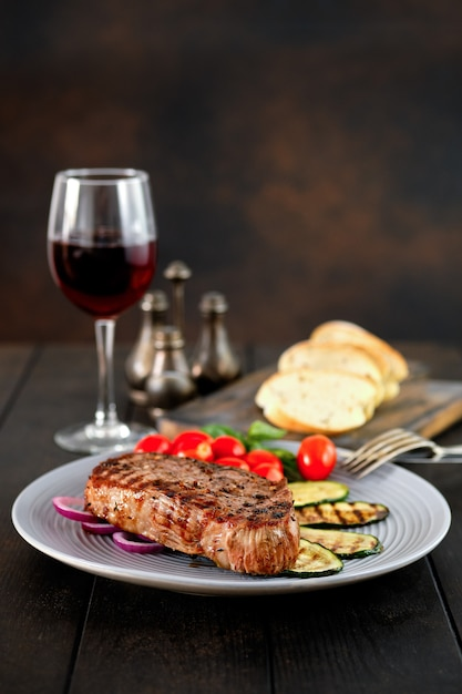 Grilled beef steak and zucchini served with fresh tomato cherry and basil and a glass of red wine Premium Photo